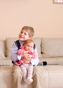 little boy and his baby sister in living room